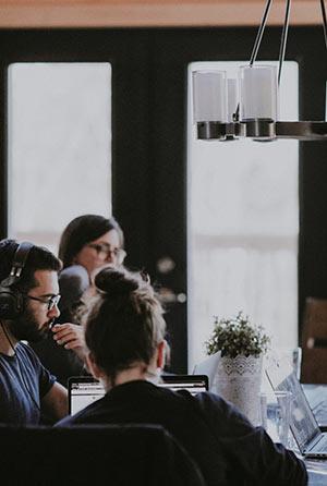 Mehrere Personen sitzen an einem Tisch und arbeiten.