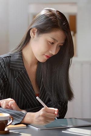 Eine Frau sitzt an einem Tisch und schreibt etwas mit einem Stift in der Hand.