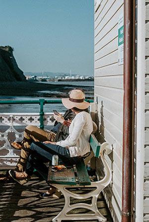 Zwei Personen, die auf einer Bank sitzen und aufs nahe gelegene Meer blicken.