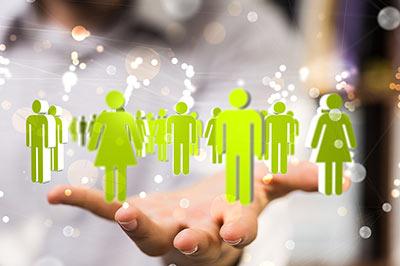 Über einer offenen Hand schweben grüne Figuren, die mit einander vernetzt sind.