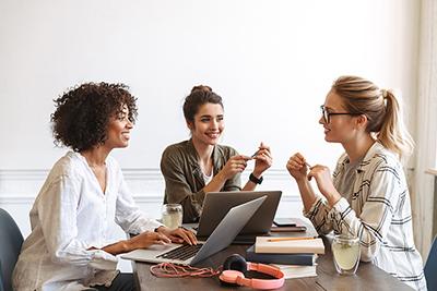Drei Frauen arbeiten gemeinsam an einem Tisch