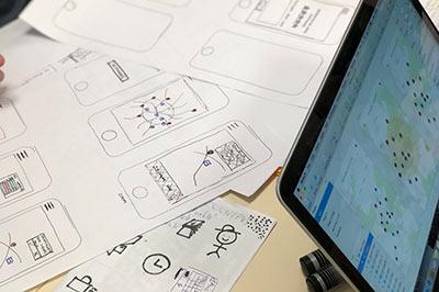 Vor einem Laptop sind auf einem Tisch mehrere Zeichnungen zum Thema UX ausgebreitet.