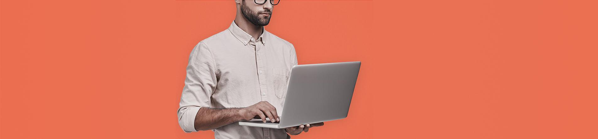 Mann mit Laptop steht vor einem roten Hintergrund.