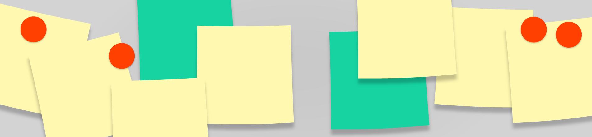 Gelbe und grüne Notizzettel an eine Pinnwand geheftet.