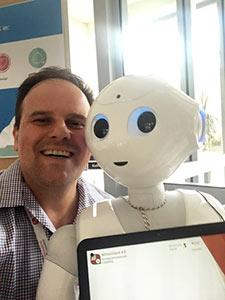 Eine Person und ein Roboter lächeln in die Kamera.