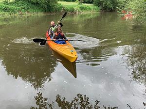 Mitarbeiter der Eresult GmbH in einem Kanu auf einem Fluss.