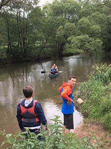 Mitarbeiter der Eresult GmbH stehen an einem Flussufer.