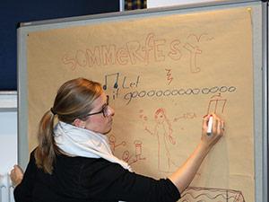 Eine Dame beschriftet ein Papier, das an einem Whiteboard befestigt ist.