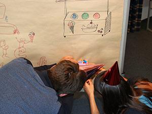 Mehrere Personen beschriften ein Papier, das an einem Whiteboard befestigt ist.