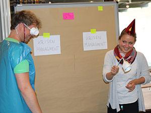 Zwei verkleiderte Mitarbeiter der Eresult GmbH stehen vor einem Whiteboard am Teamtag.