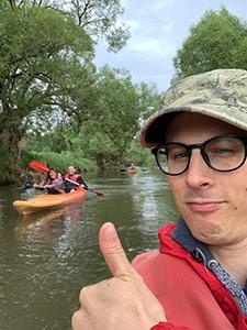 Martin Beschnitt macht ein Selfie auf einem Kanu. Im Hintergrund sind Teile des Eresult-Team auf einem weiteren Kanu.