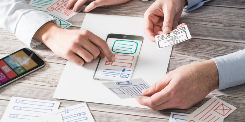 Auf dem Bild wird ein Modell einer App mit beschrifteten Papier zusammengesetzt.