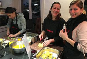 Drei Mitarbeiter kochen beim Kochkurs am Teamtag.