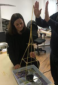 Mitarbeiter bauen ein Spagetthi-Turm am Teamtag beim Strategie-Workshop.