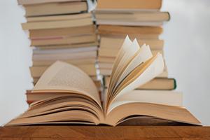 Zwei Bücherstapel und ein aufgeschlagenes Buch.