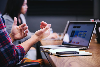 Laptop, Block und Stift liegen auf einem langen Tisch. Eine Person gestikuliert mit ihren Händen.