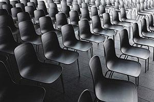 Schwarzweiß-Bild mehrere Stuhlreihen