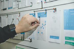 Eine Hand verbindet verschiedene Dokumente mit Fäden an einer Pinwand.