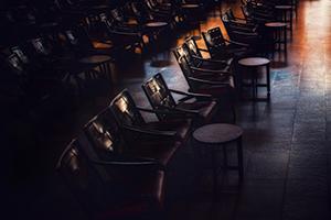 Leere Stühle und Tische im dämmrigen Licht.