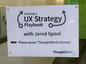 """Ein Papier mit der Beschriftung """"UX Strategy Playbook Workshop"""" hängt an einer Glaswand."""
