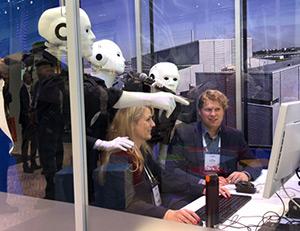 Holger Fischer sitzt mit einer weiteren Person vor einem Computer. Im Hintergrund stehen weiße Roboter.