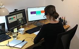 Das Bild zeigt eine Person von hinten, die an einem Computer sitzt und ein Headset trägt.