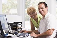 Frau und Mann sitzen am Schreibtisch und lächeln in die Kamera
