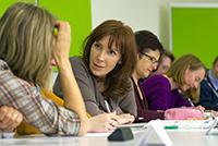 Bild der Fokusgruppe: Personen sitzen an einem länglichen Tisch und machen sich notizen oder unterhalten sich.