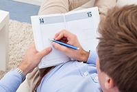 Junger Mann liegt auf dem Sofa und schreibt in sein Nutzertagebuch.