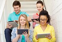 Vier Personen sitzen auf einer Treppe und sehen auf Ihre Tablets.