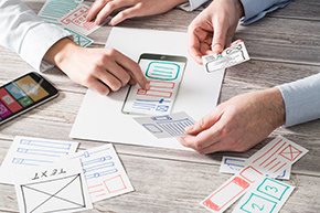 UX Konzeption anhand einer Smartphone und mehrerer App Atrappen aus Papier.