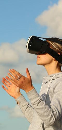 Frau mit VR-Brille auf den Augen schaut entspannt in die Zukunft