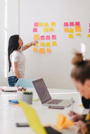 Junge Frau steht vor einem Whiteboard mit Post-Its und erklärt Zuhörern etwas