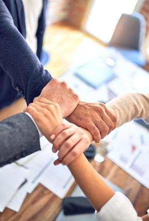 4 Hände von 4 Personen greifen ineinander