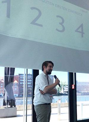 Mann mit Mikrofon spricht während eines Inhouse Seminars vor einem Publikum