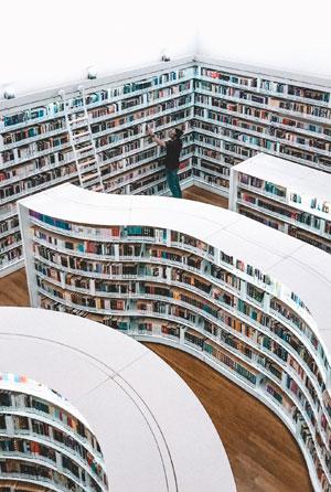 Ein Mensch greift in einer großen, modernen Bibliothek nach einem Buch