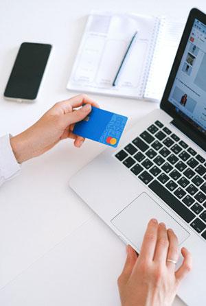 Eine Hand mit einer Kreditkarte vor einem aufgeschlagenen Laptop