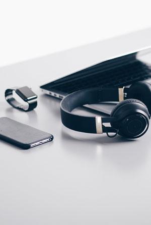 Laptop, Smartwatch, Smartphone und Kopfhörer liegen auf einem Tisch