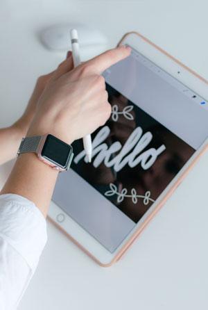 Hand mit Smartwatch am Handgelenk bedient ein Tablet