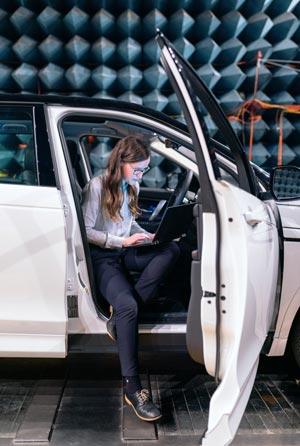 Eine junge Frau mit Laptop sitzt in einem Auto in einer Test- und Forschungshalle