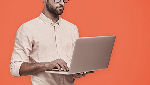 Bild zeigt Mann mit Laptop in den Händen vor einem roten Hintergrund.