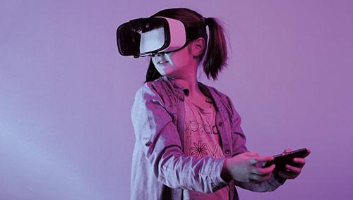 Mädchen mit aufgesetzter VR-Brille und einem Smartphone in der Hand steht vor einem lila Hintergrund.
