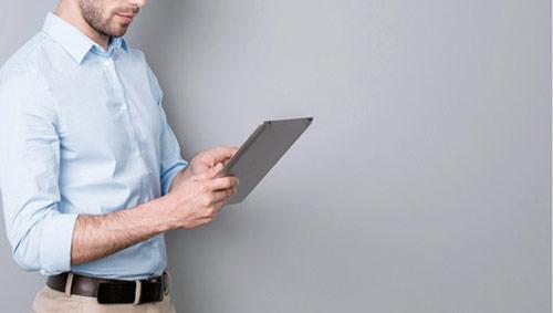Herr mit Tablet steht seitlich vor einem grauen Hintergrund.