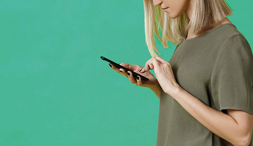 Dame mit Smartphone steht seitlich vor einem grünen Hintergrund.