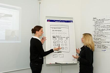 Zwei Personen stehen vor einem beschrifteten Whiteboard und unterhalten sich.