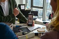 Eindrücke eines Design Thinking Workshops: Drei Menschen sitzen um ein Smartphone herum und betrachten es.