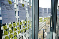Eindrücke eines Design Thinking Workshops: Dokumente in einer Reihe an Fenstern befestigt