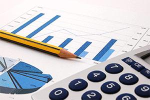 Das Bild zeigt einen Bleistift und einen Taschenrechner und auf Papier abgebildete Diagramme