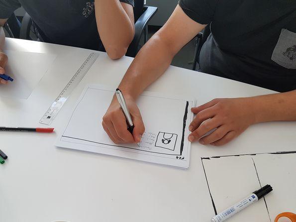 Foto eines Arms mit Stift in der Hand, die etwas auf einem weißen Blatt notiert.