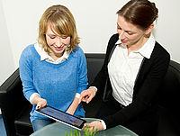 Zwei Damen sitzen nebeneinander auf einer Couch und schauen auf ein Tablet